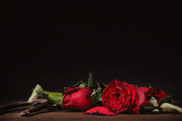 짙은 회색 배경에 시든 장미, 가을 꽃잎과 잎이 있는 나무 테이블, 슬픈 발렌타인 데이 로맨스의 디자인 컨셉, 헤어지고, 복사, 공간.