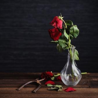 Увядшая роза на темно-сером фоне и деревянный стол с осенними лепестками и листьями, концепция дизайна грустного романтического дня святого валентина, разбитая, копия, пространство.