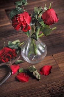 濃い灰色の背景に枯れたバラと秋の花びらと葉、悲しいバレンタインデーのロマンスのデザインコンセプト、分割、コピー、スペース。
