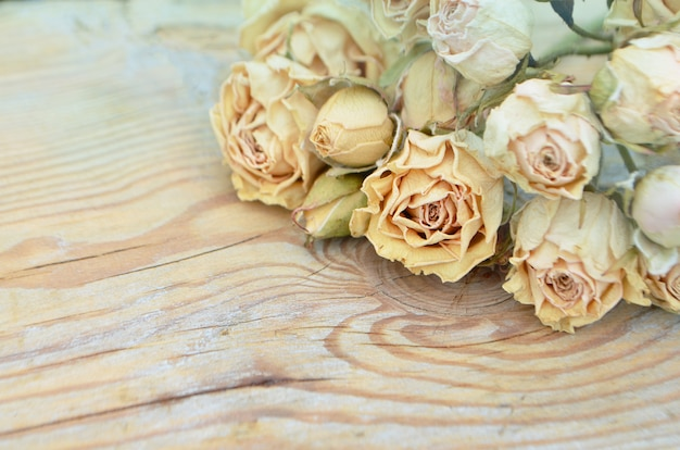 Withered rose on wooden background