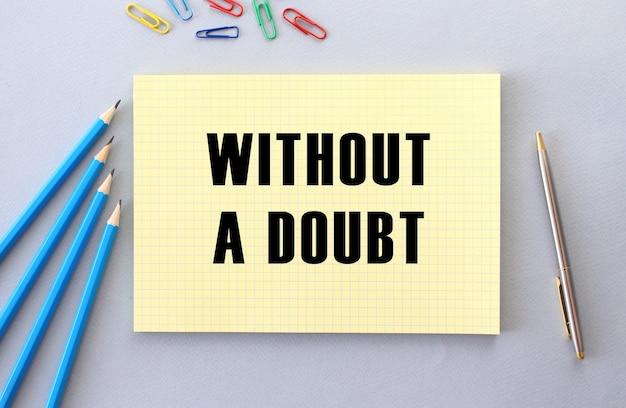 Без сомнения текст в блокноте на сером фоне рядом с карандашами, ручкой и скрепками. концепция.