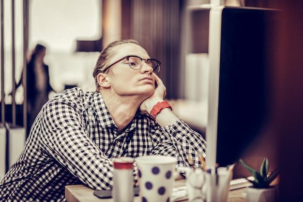興味なし。コンピューターの画面を見つめながら唇を押す疲れた男性