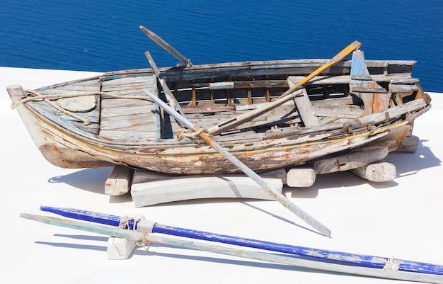 古い破損手漕ぎボートwithpaddlesとロープ