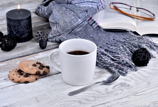 コーヒーwithscarfと白いテーブルの上のキャンドルのマグカップ