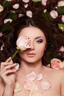 長い巻き毛と髪の明るいメイクwitjh花と美しいブルネットの女性の肖像画