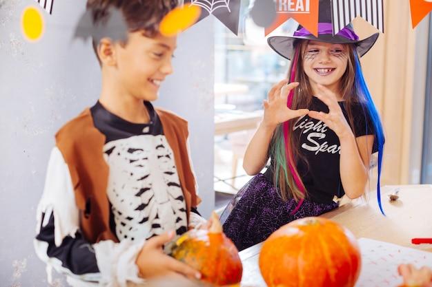 ウィザードコスチューム。面白いパーティーに出席する明るくて黒い魔法使いのハロウィーンのスーツを着て晴れやかな笑顔の女の子