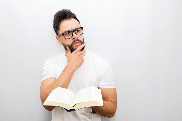 Wize and thoughtful young man in glasses stand and hold opened book in hands. he looks to side. guy holds hand on chin.