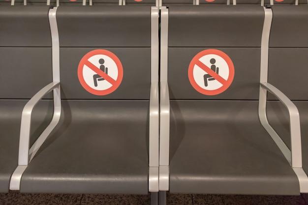 앉지 않고 거리 표지판을 유지하는 바르셀로나 출발 터미널의 공항에 2개의 좌석이 있습니다.