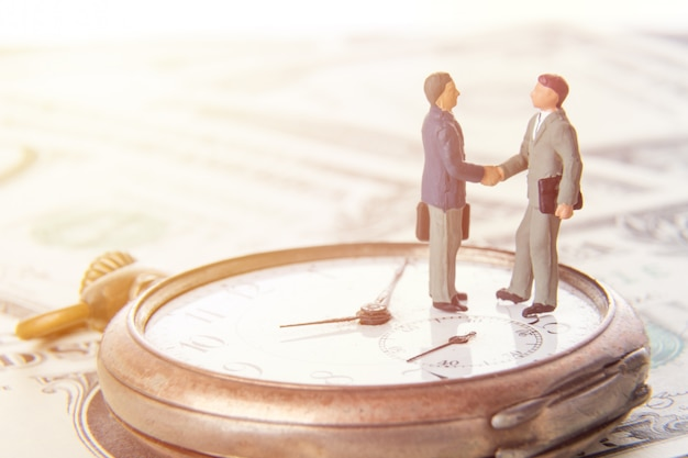 Wo миниатюрные бизнесмены, пожимая руки, стоя на старинные старинные часы и деньги американского доллара.