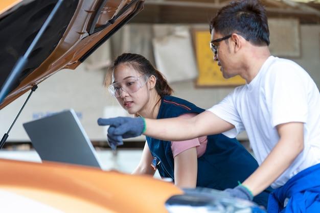 ガレージやサービスwoで車に取り組んでいる女の子エンジニア力学