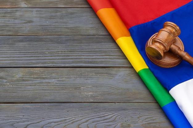 Woden judge mallet, law and justice with lgbt flag in rainbow colors and wooden background