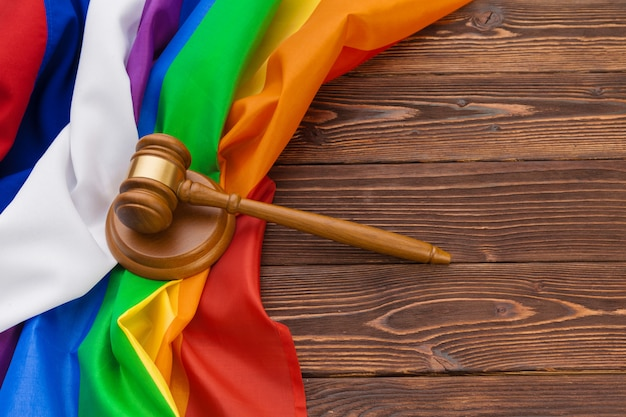 Woden judge mallet symbol of law and justice with lgbt flag in rainbow colours on wooden