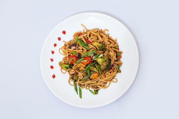 Wok food on a white ceramic plate is tasty and fresh with sauce on a light isolated background