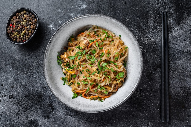 Wok hot asian cellophane noodles with chicken meat. black table. top view.