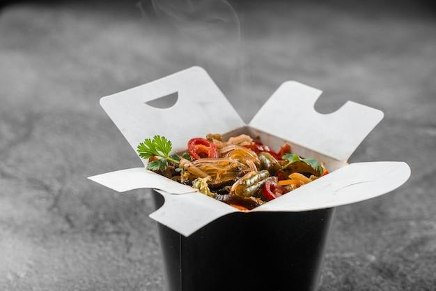 黒い食品容器に入った箱入りライスヌードルで中華鍋