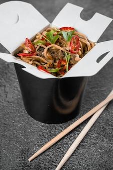 黒い食品容器に入った箱入りのスパイシーな麺で中華鍋