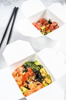 野菜、サーモン、マグロの入った紙箱の中華鍋麺。移動する屋台の食べ物、持ち帰ります。白色の背景。上面図