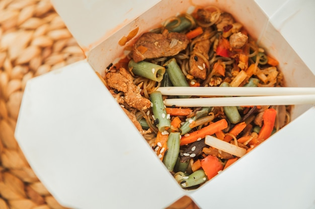 테이크 아웃 상자에 웍 국수. 북경 오리와 야채를 곁들인 밀 국수. 전통 중국 요리.