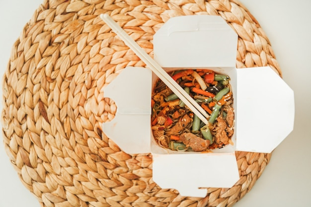 Wok noodles in takeaway box. wheat noodles with peking duck and vegetables. traditional chinese cuisine.