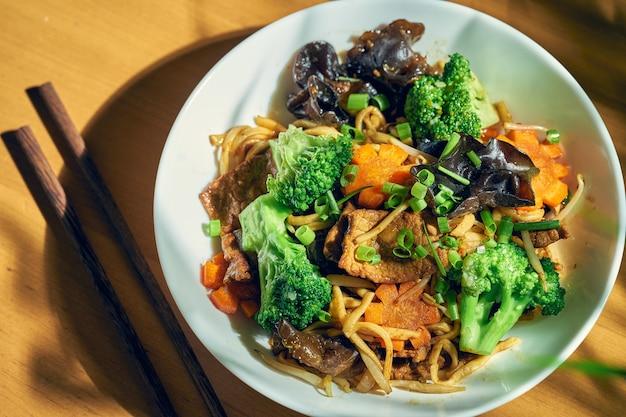 Лапша вок с говядиной, овощами, кисло-сладким соусом и сычуаньским перцем. деревянный фон. китайская кухня