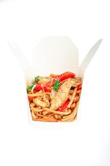 닭고기와 야채를 곁들인 웍 국수. 배송 상자에. 성분이 보입니다. 확대. 흰색 배경. 외딴.