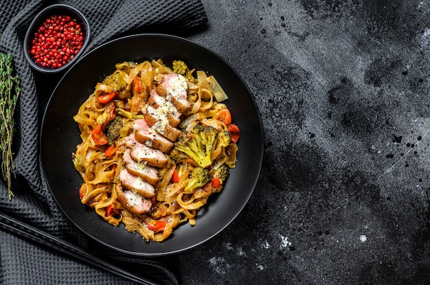 Wok noodles with duck meat and vegetables. black background. top view. copy space