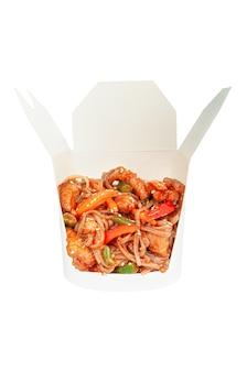 돼지고기, 야채, 핫 소스를 곁들인 웍 국수. 배송 상자에. 성분이 보입니다. 확대. 흰색 배경. 외딴.