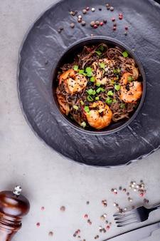 Вок лапша с креветками, в черной тарелке, украшенной горошком, на сером фоне. концепция азиатской кухни.