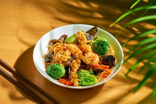 Лапша вок с овощами и морепродуктами в миске. китайская кухня