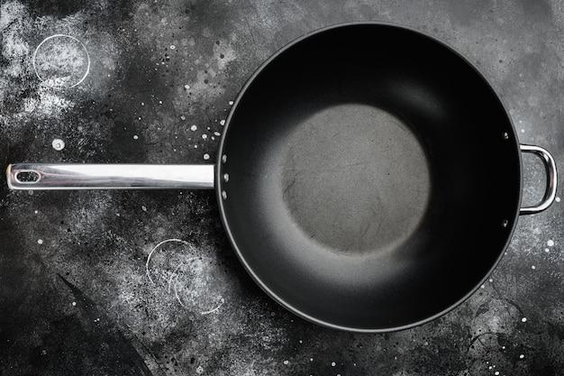 Пустой набор сковороды вок с копией пространства для текста или еды с копией пространства для текста или еды, плоский вид сверху, на черном темном каменном фоне стола