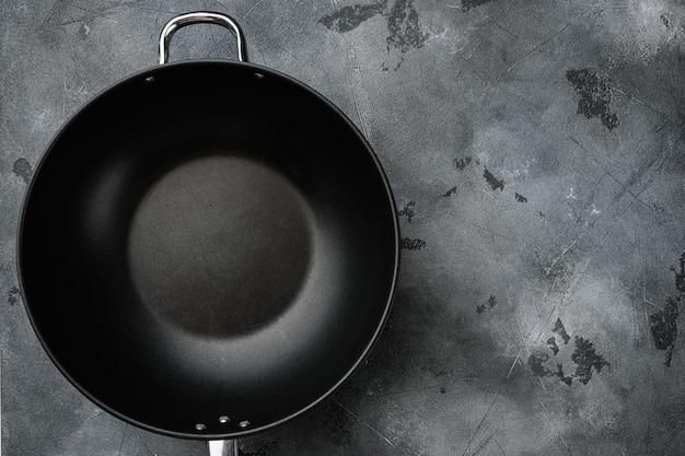 Пустой набор сковороды вок с копией пространства для текста или еды с копией пространства для текста или еды, плоский вид сверху, на фоне серого каменного стола