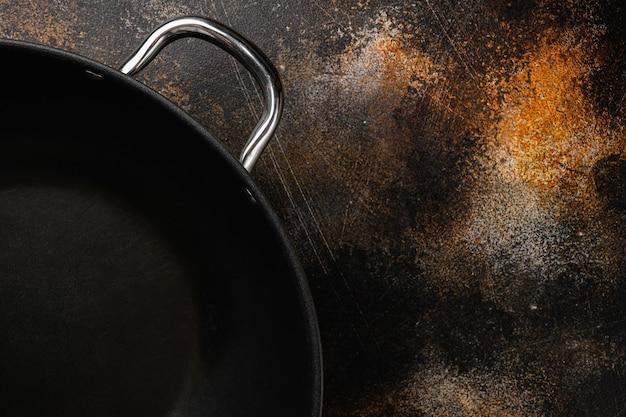 Пустой набор сковороды вок с копией пространства для текста или еды с копией пространства для текста или еды, плоский вид сверху, на старом темном деревенском фоне стола