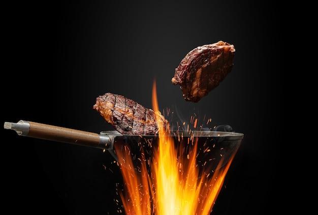 불 위에 연기가 나는 냄비 팬이 검은 스튜디오 배경 요리 배경에 대해 두 개의 쇠고기 스테이크를 튀기고 있습니다...