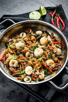 Wok with stir fry udon noodles, cuttlefish and vegetables.