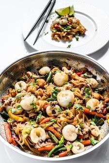 炒め物うどん、魚介類、野菜を中華鍋で。白色の背景。上面図