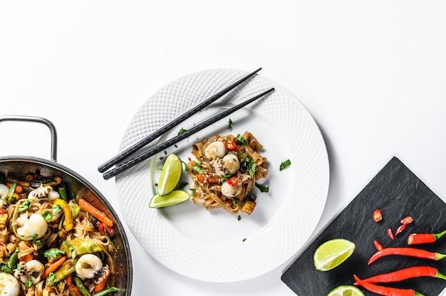 炒めうどん、魚介類、野菜を炒めた中華鍋。白色の背景