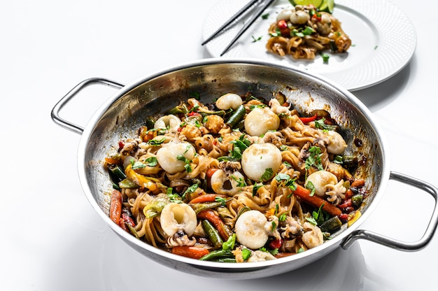 Wok with stir fry udon noodles, seafood and vegetables. white background. top view