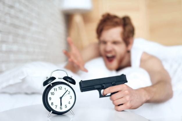 Woken up evil man is aims gun at alarm clock, lying in bed