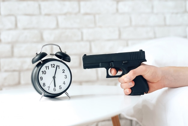 Woken up man is aims gun at alarm clock