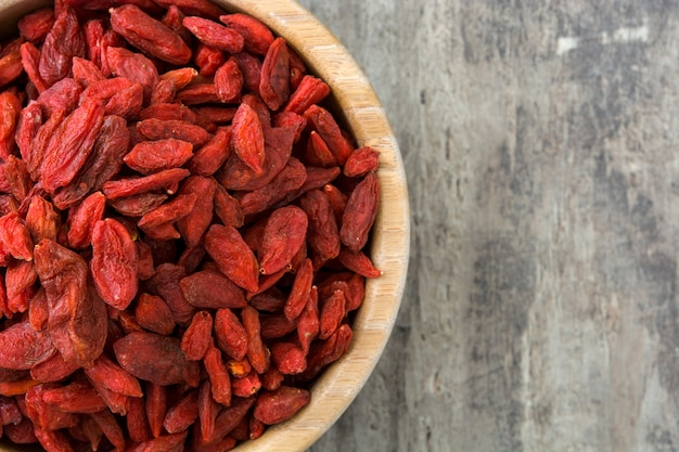 Wolfberries or goji berries in bowl on wooden surface top view