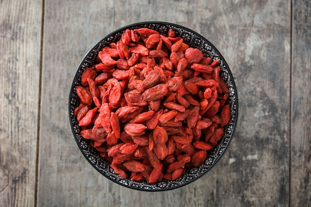 Wolfberries or goji berries in bowl on wooden table top view