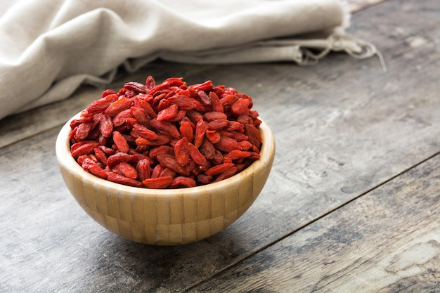 Wolfberries or goji berries in wooden bowl on wooden table copy space