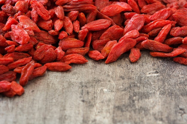 Wolfberries or goji berries on wooden table copy space
