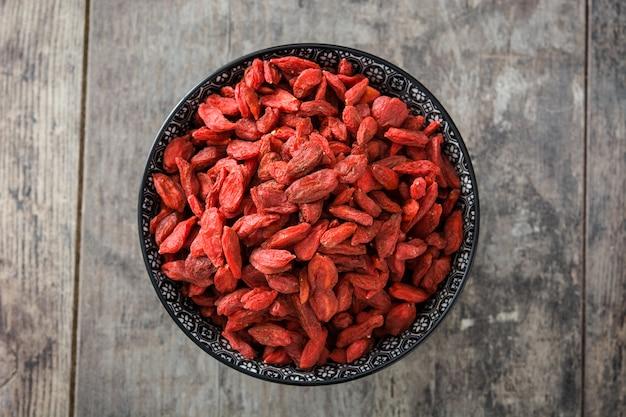 Wolfberries или ягоды годжи в миску на вид сверху деревянный стол