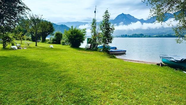 ヴォルフガングゼー夏の湖の曇りの景色(オーストリア)と岸に2羽の白鳥。