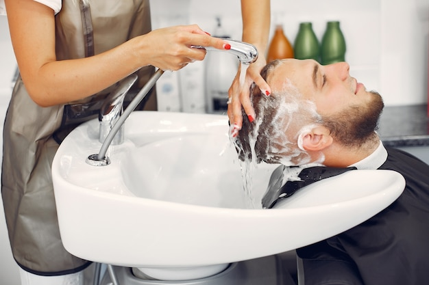 Woma washing man's head in a barbershop