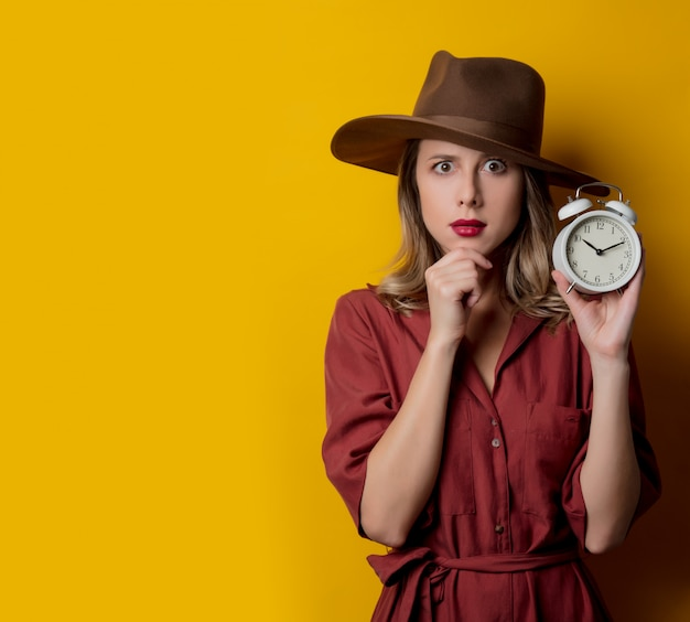 Woman in 1940s style clothes with alarm clock