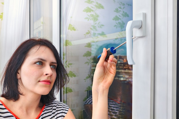 Woman of 20 years old uninstalls handle on double-glazed window frame, using  screwdriver.