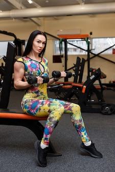 Женщина 30 лет с гантелями на тренировке в тренажерном зале