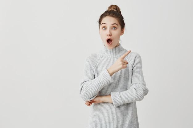 口を開けて立っている30代の女性と刺激的な何かで人差し指を示しています。ショックを受けて興奮している女子学生の面白い感情。アミューズメントのコンセプト